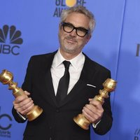 Alfonso Cuarón poses with two Golden Globes