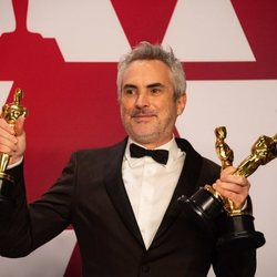 Alfonso Cuarón poses with his three Oscars