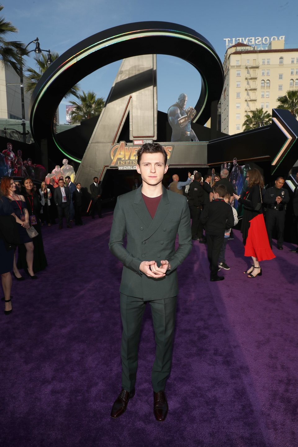 Tom Holland poses on the purple carpet at the world premiere of 'Avengers: Infinity War'