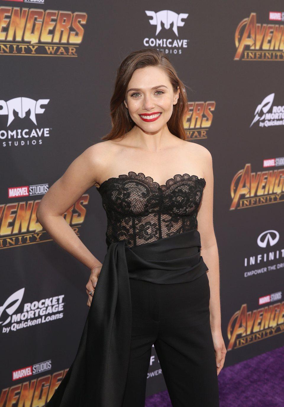 Elizabeth Olsen poses on the purple carpet at the world premiere of 'Avengers: Infinity War'